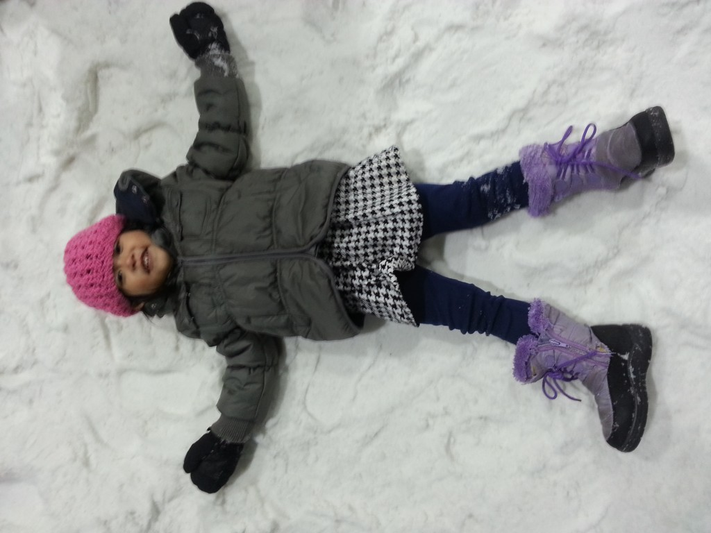 The little girl making a snow angel